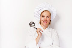 Young woman chef holding ladle, smiling. Royalty Free Stock Photography