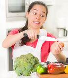 Young woman chef holding up kitchen knife and egg, interacting with facial expressions, vegetables on desk in front Stock Images