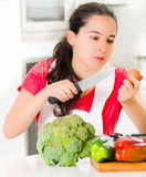 Young woman chef holding up kitchen knife and egg, interacting with facial expressions, vegetables on desk in front Royalty Free Stock Photos