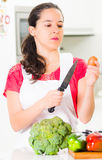 Young woman chef holding up kitchen knife and egg, interacting with facial expressions, vegetables on desk in front Stock Image