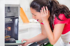 Young woman chef looking into oven with frustrated facial expression, holding black burnt bread on tray Stock Photo