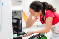 Young woman chef looking into oven with frustrated facial expression, holding black burnt bread on tray Royalty Free Stock Photography