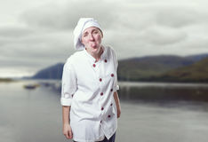 Young woman chef making a joke gesture with her tongue.  Royalty Free Stock Photography