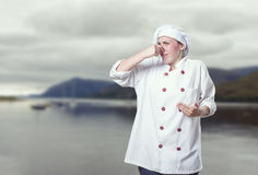 Young woman chef making smell bad gesture. Young woman chef making smell bad gesture royalty free stock photos
