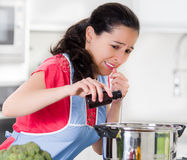 Young woman chef pouring extract from small bottle into silver kettle with skeptical facial expression Stock Photos