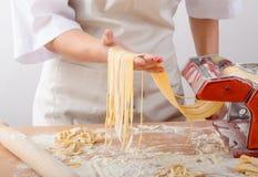 Young woman chef prepares homemade pasta Stock Photos
