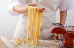 Young woman chef prepares homemade pasta Royalty Free Stock Image