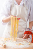 Young woman chef prepares homemade pasta Royalty Free Stock Photography