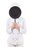 Young woman in chef uniform with frying pan behind her face isol Royalty Free Stock Photo