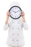 Young woman chef in uniform holding office clock behind her face Royalty Free Stock Images