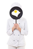 Young woman in chef uniform holding skillet with frying egg behi Royalty Free Stock Photography