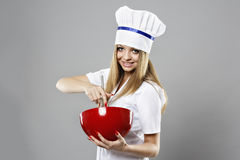 Young woman in chef uniform mixing something in red  bowl isolat Royalty Free Stock Photos