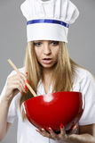 Young woman in chef uniform mixing something in red bowl Stock Photography