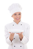 Young woman chef in uniform showing empty plate isolated on whi. Te background stock photos