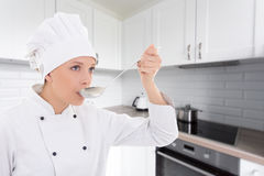 Young woman in chef uniform tasting something in kitchen Stock Image