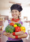Young woman chef wearing traditional andean blouse, black cooking hat, holding broccoli, capsicum, tomato and lemon Royalty Free Stock Images