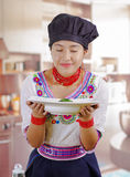 Young woman chef wearing traditional andean blouse, black cooking hat, holding deep white plate, leaning over smelling Stock Photography