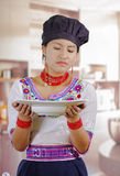 Young woman chef wearing traditional andean blouse, black cooking hat, holding deep white plate, looking at soup with Royalty Free Stock Photo