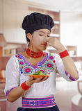 Young woman chef wearing traditional andean blouse, black cooking hat, holding plate of cucumber slices, covering nose Stock Photos