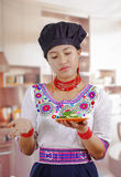 Young woman chef wearing traditional andean blouse, black cooking hat, holding plate of cucumber slices, skeptic facial. Expression, kitchen background Stock Photos
