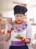 Young woman chef wearing traditional andean blouse, black cooking hat, holding plate of cucumber slices, skeptic facial. Expression, kitchen background Royalty Free Stock Image