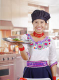 Young woman chef wearing traditional andean blouse, black cooking hat, holding up large tray with cucumber slices on top Stock Photography