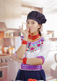 Young woman chef wearing traditional andean blouse, black cooking hat, touching lips with fingers for camera, kitchen Stock Image