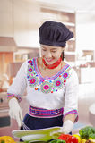 Young woman chef wearing traditional andean blouse, black cooking hat, vegetables on desk, holding deep plate and whisk Stock Photos