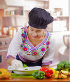 Young woman chef wearing traditional andean blouse, black cooking hat, vegetables on desk, placing green leaf inside Royalty Free Stock Photography