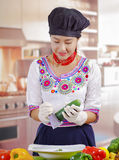 Young woman chef wearing traditional andean blouse, black cooking hat, vegetables on desk, shredding cucumber into deep Royalty Free Stock Photography