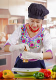 Young woman chef wearing traditional andean blouse, black cooking hat, vegetables on desk, using pepper mill over deep Royalty Free Stock Photography