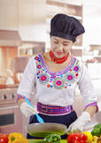 Young woman chef wearing traditional andean blouse, black cooking hat, vegetables on desk, using skillet and spatula royalty free stock image