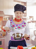 Young woman chef wearing traditional andean blouse and cooking hat, vegetables on desk, holding cook pot with sauce Stock Images