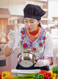 Young woman chef wearing traditional andean blouse and cooking hat, vegetables on desk, holding spoon, cook pot in other Stock Photography
