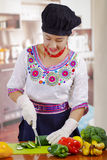 Young woman chef wearing traditional andean blouse and cooking hat, vegetables on desk, using knife chopping cucumber Stock Images