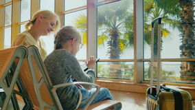 Young woman with child in airport waiting room. A girl of 6 years in glasses uses a tablet. Palm trees grow outside the. Window and the sun is shining. 4K video stock video footage