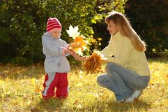 Young woman and child collect autumn sheets. In park stock images