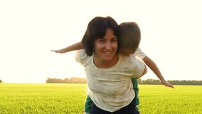 Young woman and child having fun outdoors. Beautiful family mom and her boy boy hugging and kissing together. Mom keeps stock video footage