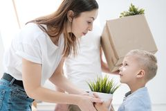 A young woman and child are holding a cardboard box with things on a white background. stock photo