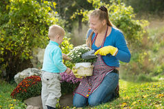Young woman with a child are planting flowers Stock Image