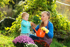Young woman with a child are planting flowers Royalty Free Stock Image