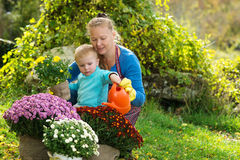 Young woman with a child are planting flowers Royalty Free Stock Photos
