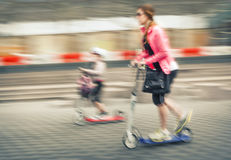 Young woman and child riding on scooters Stock Images