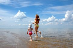 The young woman with the child runing on water Royalty Free Stock Image