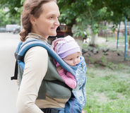 The young woman with the child on sling Stock Photos