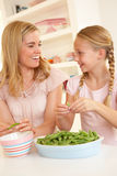 Young woman with child splitting pea in kitchen Stock Photography