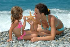 Young woman and child with starfish Royalty Free Stock Photography
