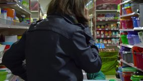 A young woman with a child in a supermarket chooses goods. Mom is driving a little girl on a trolley. Consider the goods. In the department of utensils. The stock video
