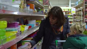 A young woman with a child in a supermarket chooses goods. Mom is driving a little girl on a trolley. Consider the goods. In the department of utensils. 4K stock video