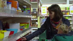A young woman with a child in a supermarket chooses goods. Mom is driving a little girl on a trolley. Consider the goods. In the department of utensils. 4K stock footage
